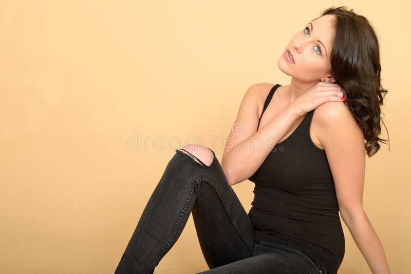Mujer joven pensativa atractiva atractiva que lleva vaqueros y el top negros del chaleco imagenes de archivo