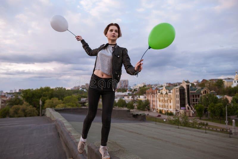 Mujer joven pensativa con dos globos del juguete imagen de archivo libre de regalías