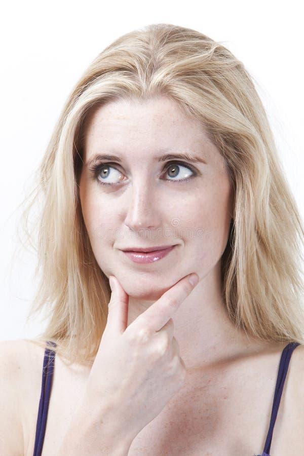 Mujer joven pensativa con la mano en la barbilla que mira lejos contra el fondo blanco fotos de archivo