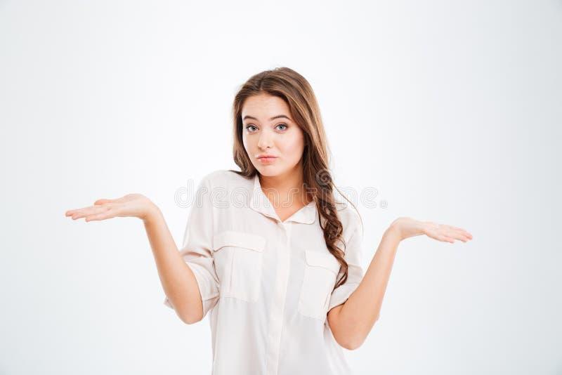 Mujer joven pensativa confusa que lleva a cabo el copyspace en ambas palmas fotos de archivo libres de regalías