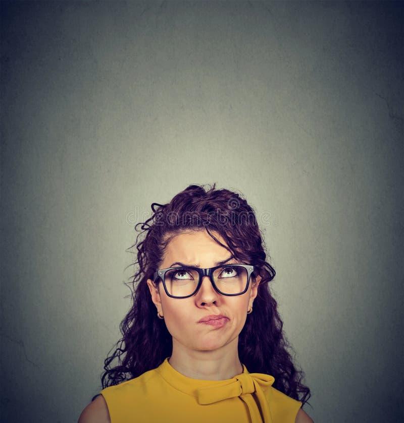 Mujer joven pensativa dudosa que mira para arriba imagen de archivo
