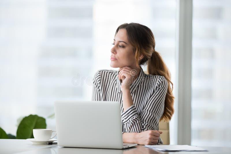 Mujer joven pensativa enfocada que mira en distancia foto de archivo