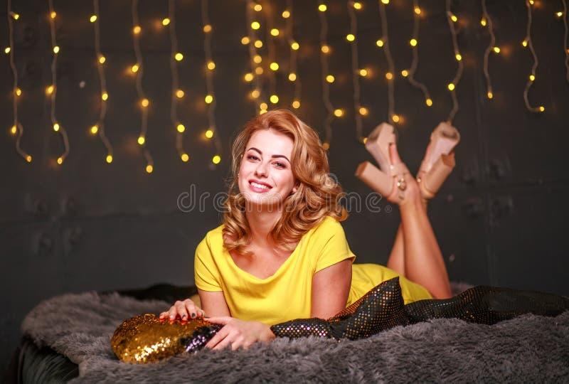 Mujer joven pensativa feliz en fondo festivo de las luces del sofá imagenes de archivo