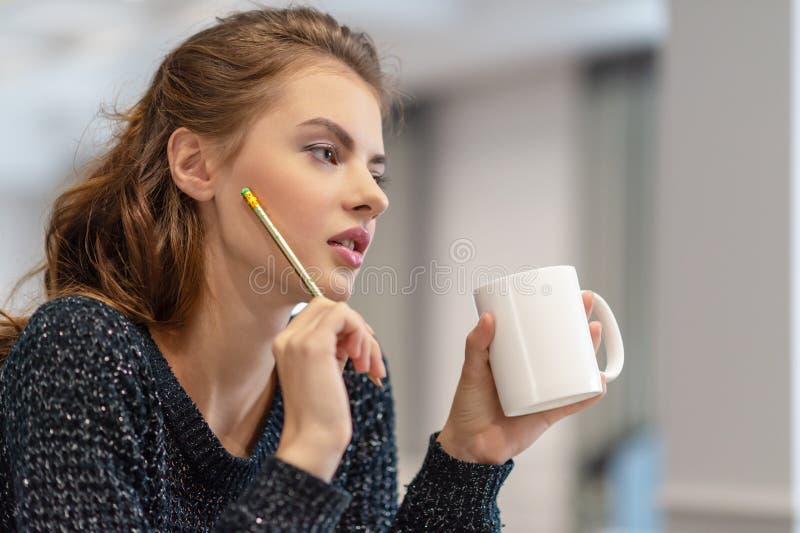 Mujer joven pensativa que hace notas usando la libreta en cocina imagenes de archivo