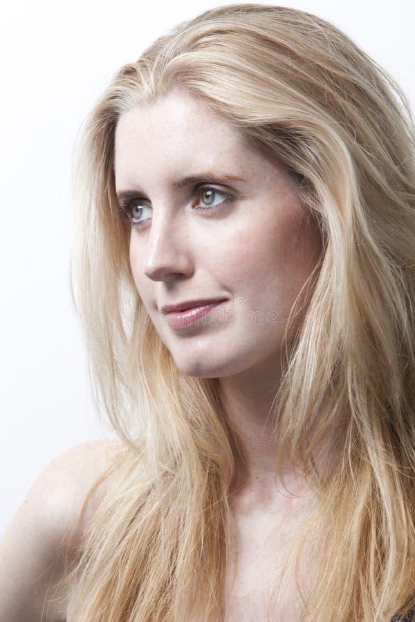 Mujer joven pensativa que mira lejos contra el fondo blanco imagenes de archivo