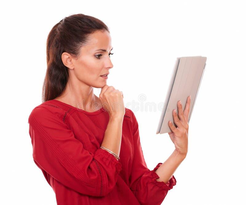 Mujer joven pensativa que mira su PC de la tableta fotografía de archivo