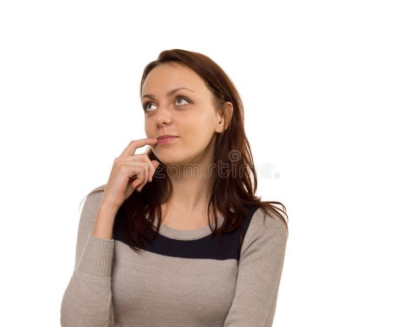 Mujer joven pensativa que se coloca que sueña despierto imagenes de archivo