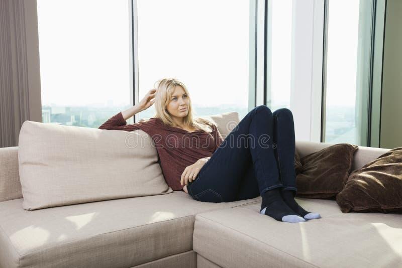Mujer joven pensativa que se sienta en el sofá contra ventana en casa fotos de archivo libres de regalías