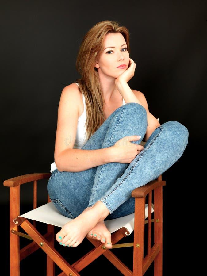 Mujer joven pensativa relajada hermosa que se sienta en una silla imagen de archivo