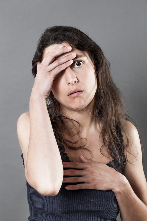 Mujer joven perdida que mira tenencia desesperada y desilusionada su cabeza fotos de archivo