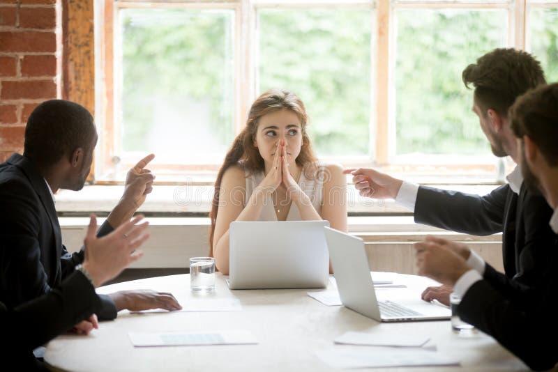 Mujer joven perpleja que mira a los compañeros de trabajo que señalan los fingeres en h imagen de archivo libre de regalías