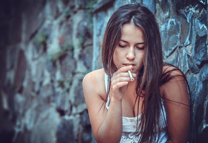 Mujer joven pobre con un cigarrillo imagenes de archivo