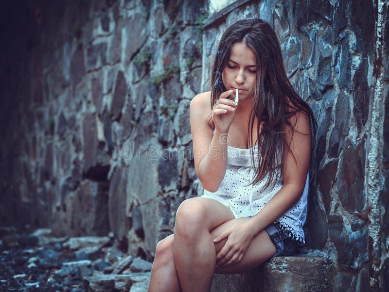 Mujer joven pobre con un cigarrillo foto de archivo