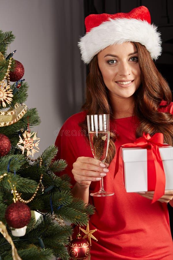 Mujer joven por un christmastree imagen de archivo