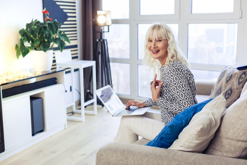 Mujer joven positiva alegre que trabaja de hogar foto de archivo libre de regalías