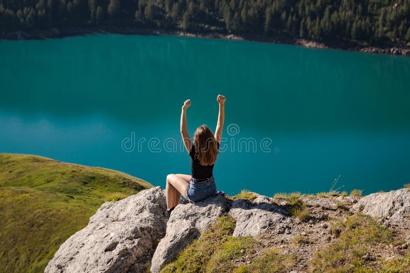 Mujer joven positiva que disfruta de la libertad en el top de la montaña con el ritom del lago como fondo imagenes de archivo
