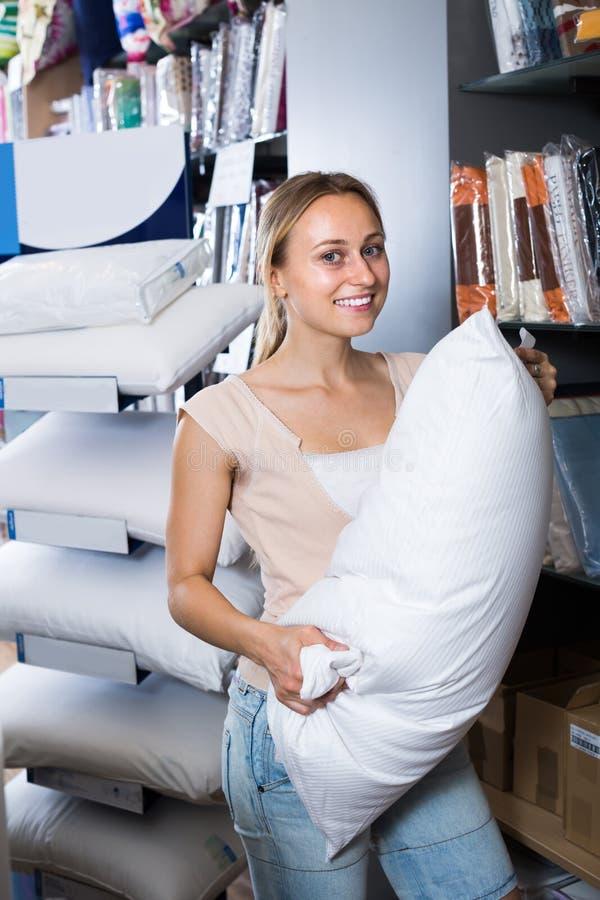 Mujer joven positiva que elige la almohada suave imágenes de archivo libres de regalías