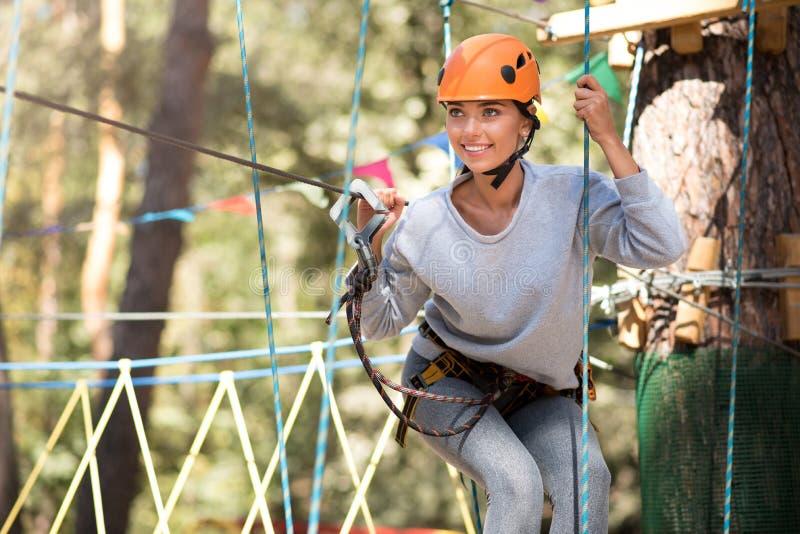 Mujer joven positiva que se goza en el parque del cable de alta tensión imagenes de archivo
