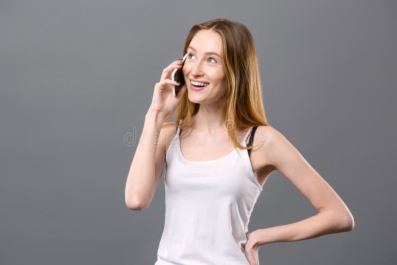 Mujer joven positiva que tiene una conversación telefónica imagen de archivo