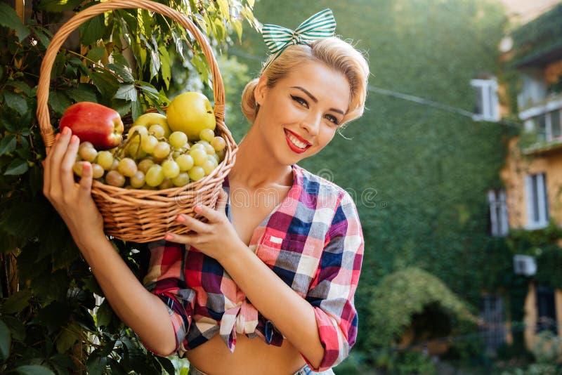 Mujer joven preciosa alegre que sostiene la cesta de frutas frescas imagenes de archivo