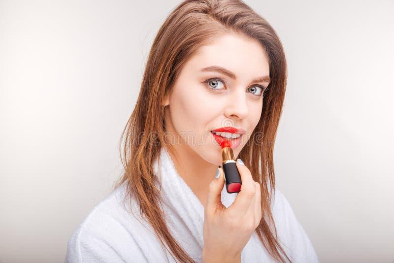 Mujer joven preciosa atractiva que prueba el lápiz labial rojo en sus labios imagen de archivo
