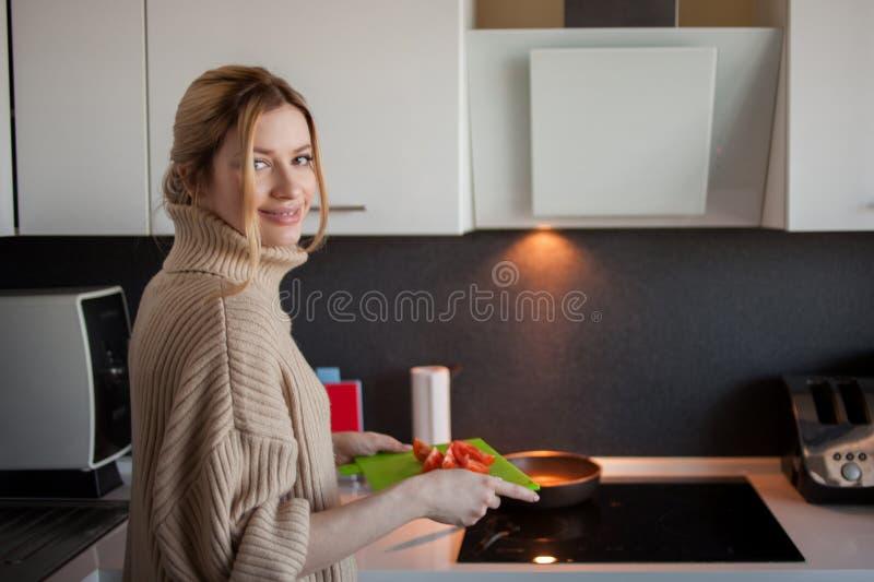 Mujer joven preciosa en casa en la cocina, verduras de los cortes, ingredientes para el plato Consumici?n sana como forma de vida imagen de archivo libre de regalías