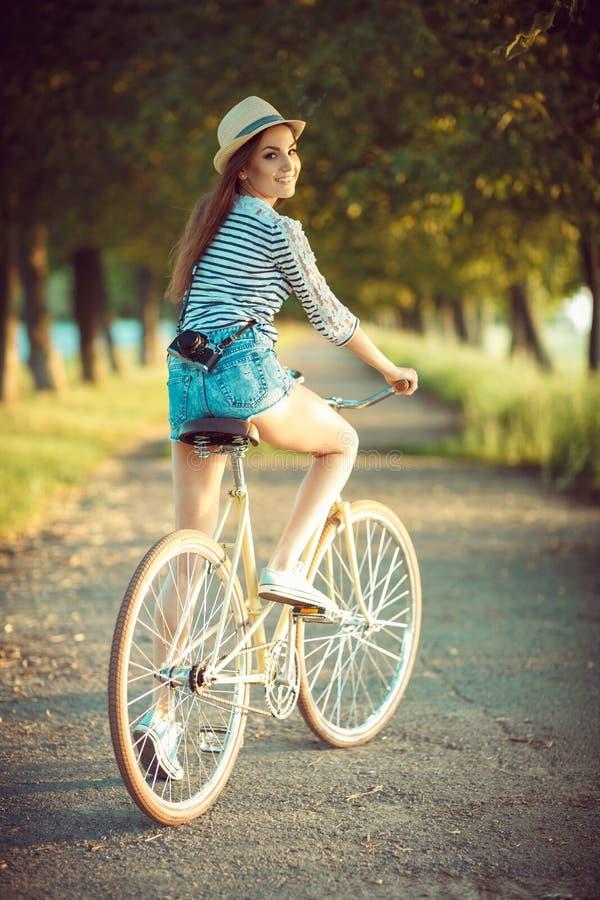 Mujer joven preciosa en un sombrero que monta una bicicleta en un parque fotos de archivo