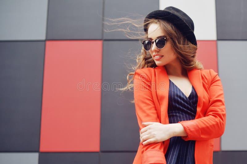 Mujer joven preciosa linda en gafas de sol, chaqueta roja, sombrero de la moda, colocándose sobre el fondo abstracto al aire libr imagen de archivo libre de regalías