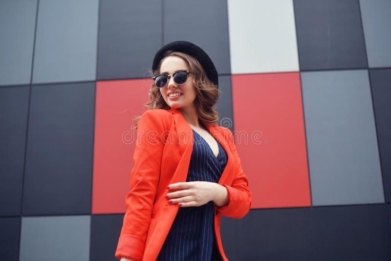 Mujer joven preciosa linda en gafas de sol, chaqueta roja, sombrero de la moda, colocándose sobre el fondo abstracto al aire libr imágenes de archivo libres de regalías