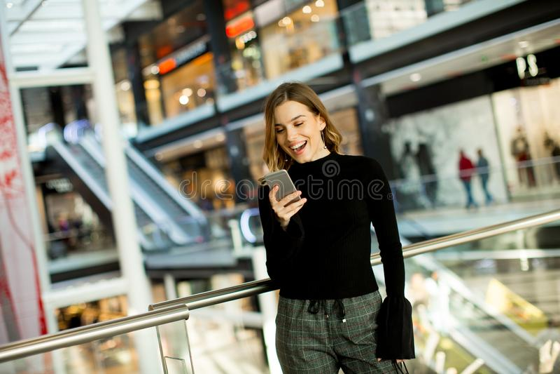 Mujer joven preciosa que mira en el teléfono móvil en centro comercial fotos de archivo