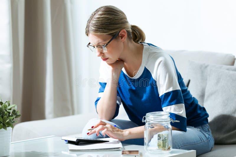 Mujer joven preocupante usando la calculadora y la cuenta de sus ahorros mientras que se sienta en el sofá en casa imagenes de archivo