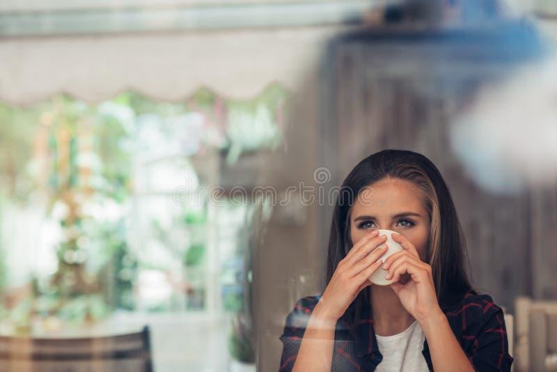 Mujer joven profundamente en el pensamiento que bebe un café fotos de archivo libres de regalías