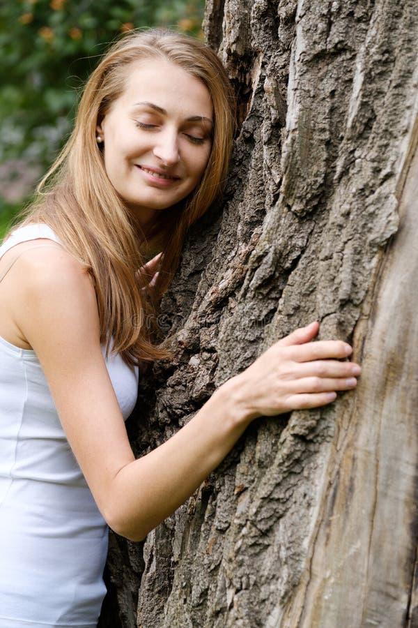 Mujer joven que abraza el árbol grande imagen de archivo