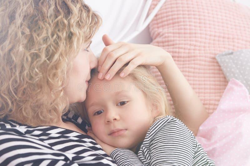 Mujer joven que abraza a su hija imágenes de archivo libres de regalías