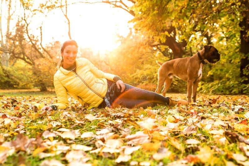Mujer joven que abraza su perro en el parque imagen de archivo