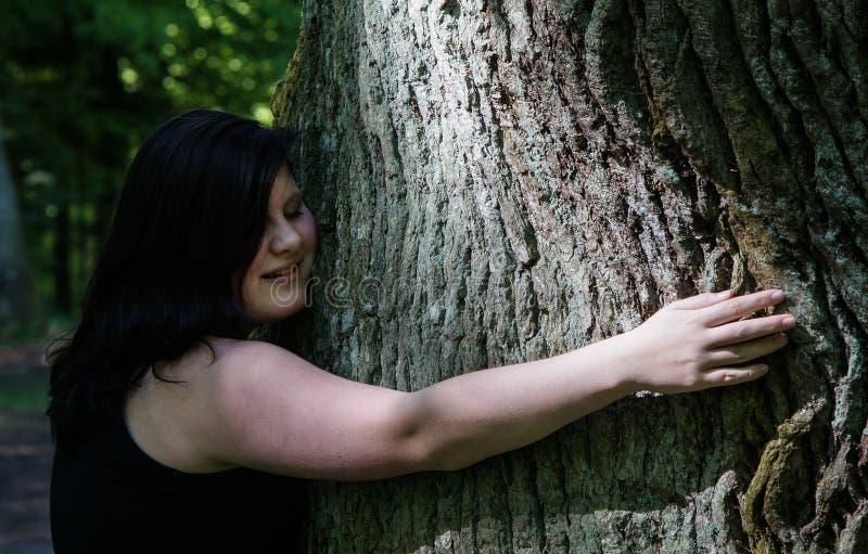Mujer joven que abraza un árbol foto de archivo