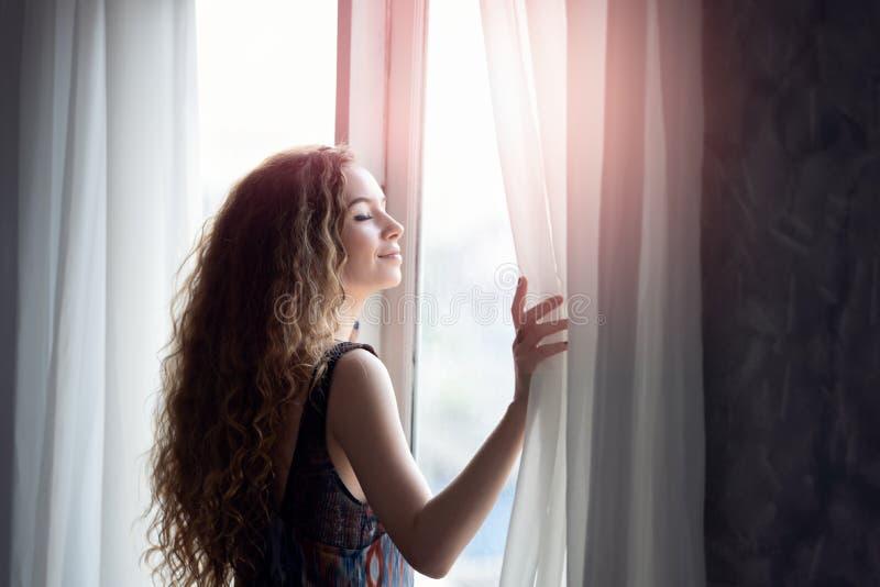 Mujer joven que abre la cortina por la ma?ana fotos de archivo
