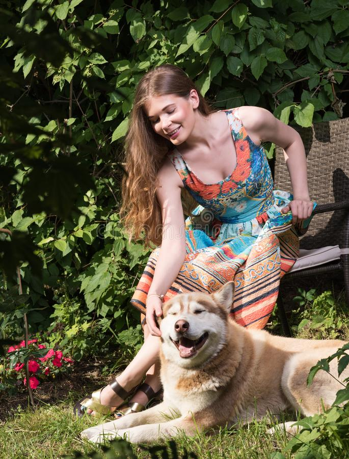 Mujer joven que acaricia un perro Retrato del verano al aire libre fotos de archivo libres de regalías