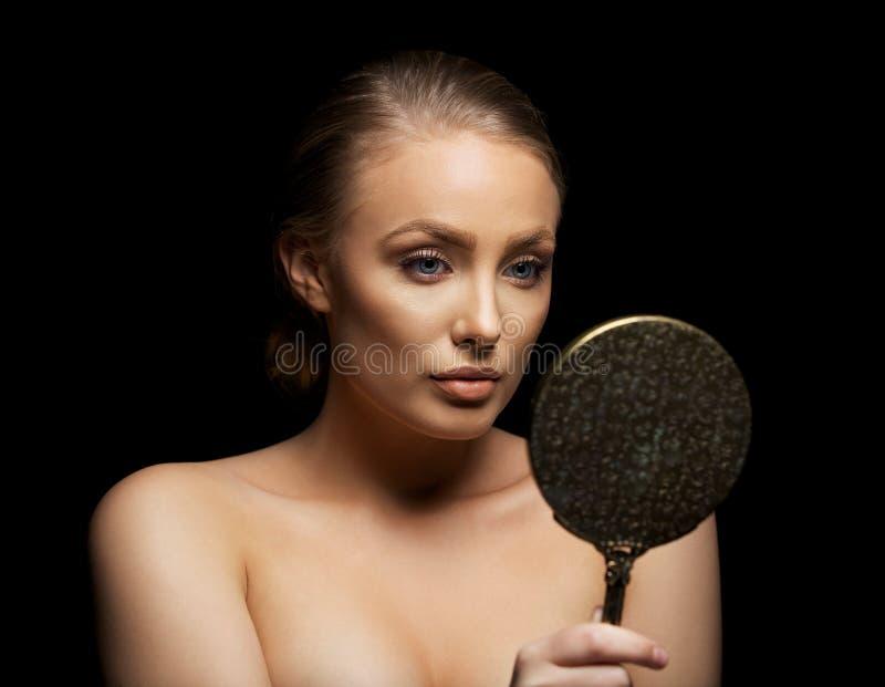 Mujer joven que admira su piel perfecta en un espejo fotografía de archivo libre de regalías