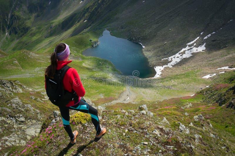 Mujer joven que admira un lago glacial hermoso imagen de archivo libre de regalías