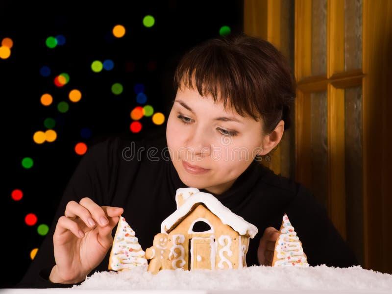 Mujer joven que adorna la casa de pan de jengibre imagenes de archivo