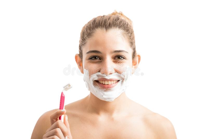 Mujer joven que afeita su cara foto de archivo