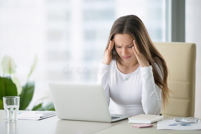 Mujer joven que agarra la cabeza con un dolor cerca del ordenador portátil fotos de archivo