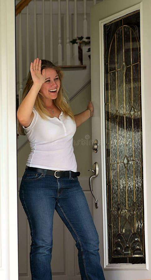 Mujer joven que agita en la puerta principal foto de archivo libre de regalías