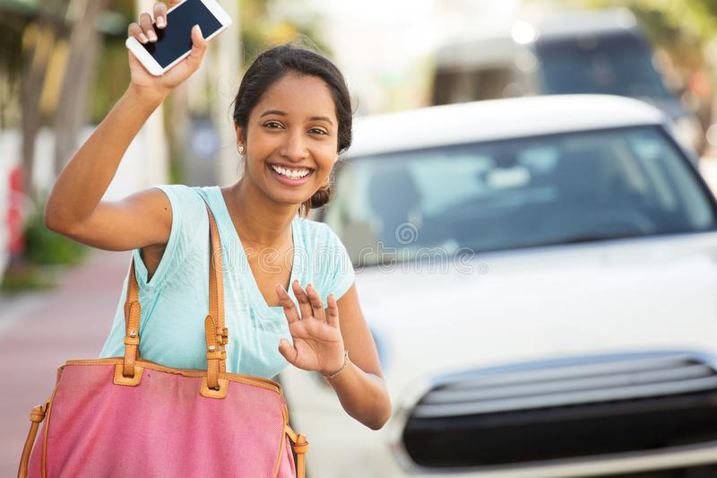 Mujer joven que agita su mano para su paseo foto de archivo