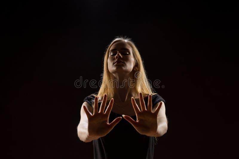 Mujer joven que agita sus manos Muchacha rubia que expresa con las manos aumentadas sus emociones en un estudio en un fondo negro fotos de archivo libres de regalías