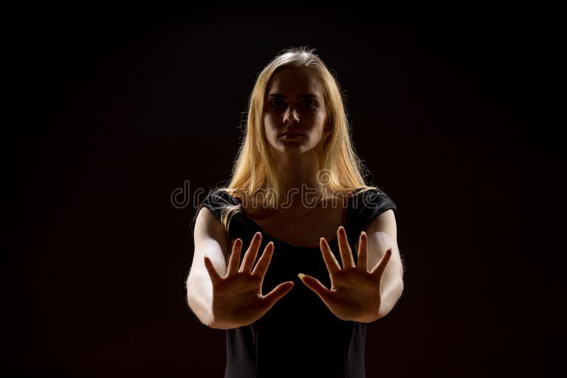 Mujer joven que agita sus manos Muchacha rubia que expresa con las manos aumentadas sus emociones en un estudio en un fondo negro imagen de archivo