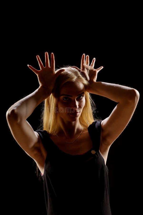 Mujer joven que agita sus manos Muchacha rubia que expresa con las manos aumentadas sus emociones en un estudio en un fondo negro imagen de archivo libre de regalías