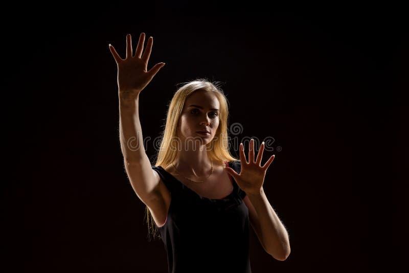 Mujer joven que agita sus manos Muchacha rubia que expresa con las manos aumentadas sus emociones en un estudio en un fondo negro imágenes de archivo libres de regalías