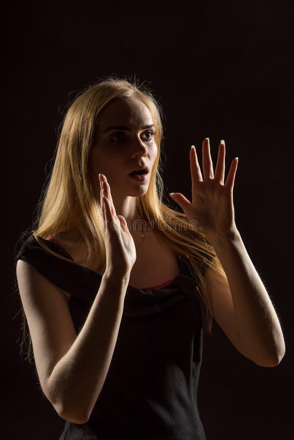 Mujer joven que agita sus manos Muchacha rubia que expresa con las manos aumentadas sus emociones en un estudio en un fondo negro fotografía de archivo